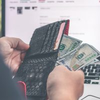 Person holding cash in front of laptop