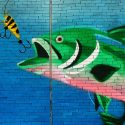Fish about to eat a hook wall art on bricks